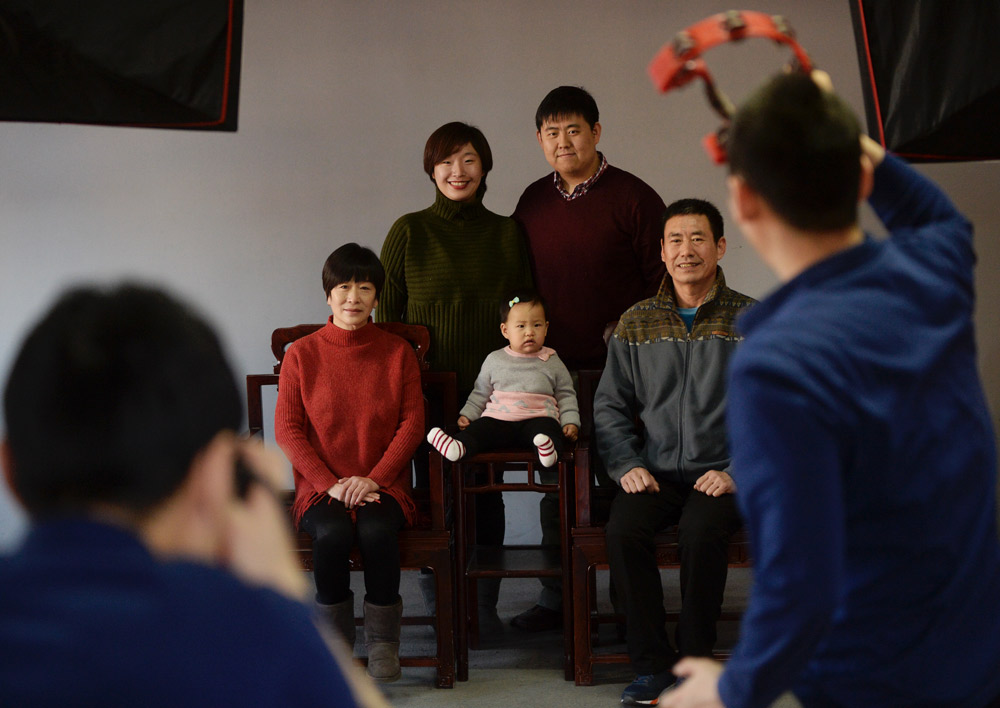 A family poses for a family portrait at a photo studio in Beijing, 2017. Hao Yi and Wang Weiwen/Beijing Youth Daily/People Visual