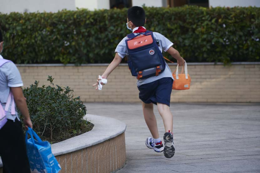A boy runs to the entrance of the Primary School Affiliated to Shanghai University, Sept. 1, 2021. Wu Huiyuan/Sixth Tone