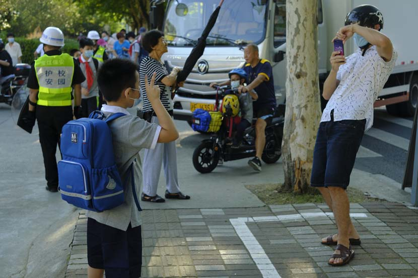 A father takes photos of his son outside the Primary School Affiliated to Shanghai University, Sept. 1, 2021. Wu Huiyuan/Sixth Tone
