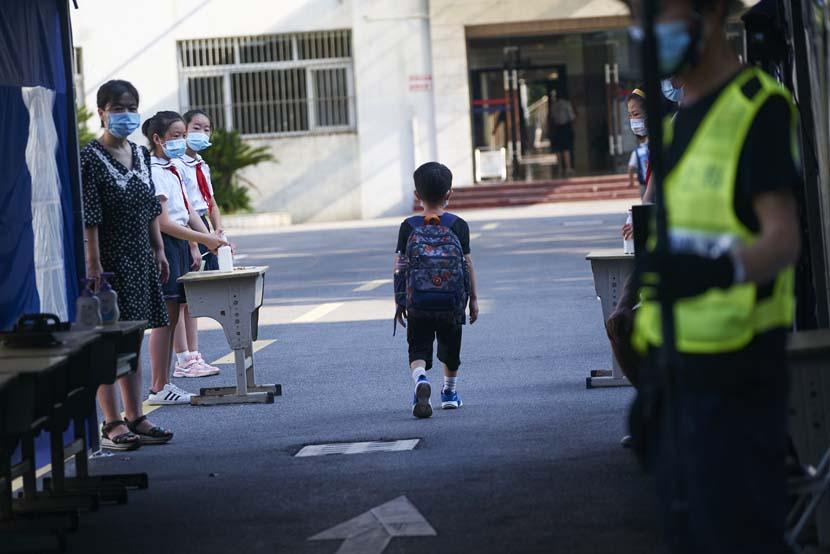 A boy enters a private school in Shanghai, Sept. 1, 2021. Wu Huiyuan/Sixth Tone