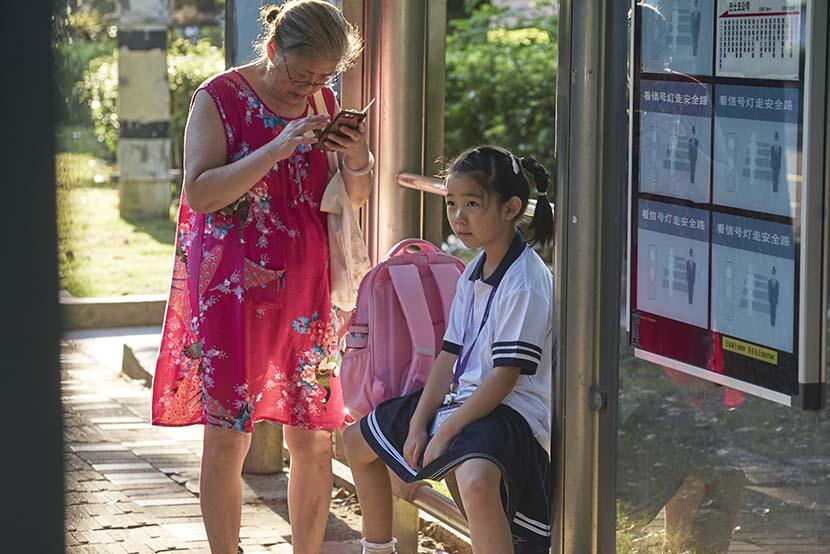 A girl waits at a bus station in Shanghai, Sept. 1, 2021. Wu Huiyuan/Sixth Tone