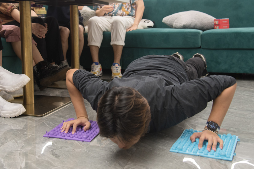 A butler does push-ups after losing a game at the café, Shanghai, August 2021. Xie Anran/Sixth Tone