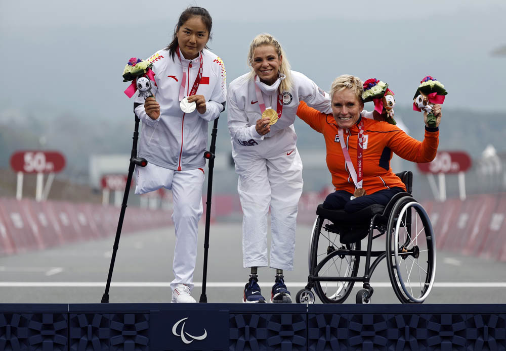 From left to right, silver medalist Sun Bianbian of China, gold medalist Oksana Masters of the United States, and bronze medalist Jennette Jansen of the Netherlands celebrate after the women's cycling H4-5 time trial in Shizuoka, Japan, Aug. 31, 2021. Issei Kato/Reuters via IC
