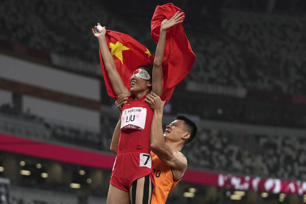 Liu Cuiqing celebrates with her guide, Xu Donglin, after winning the women's T11 200-meter final in Tokyo, Japan, Sept. 4, 2021. Emilio Morenatti via People Visual