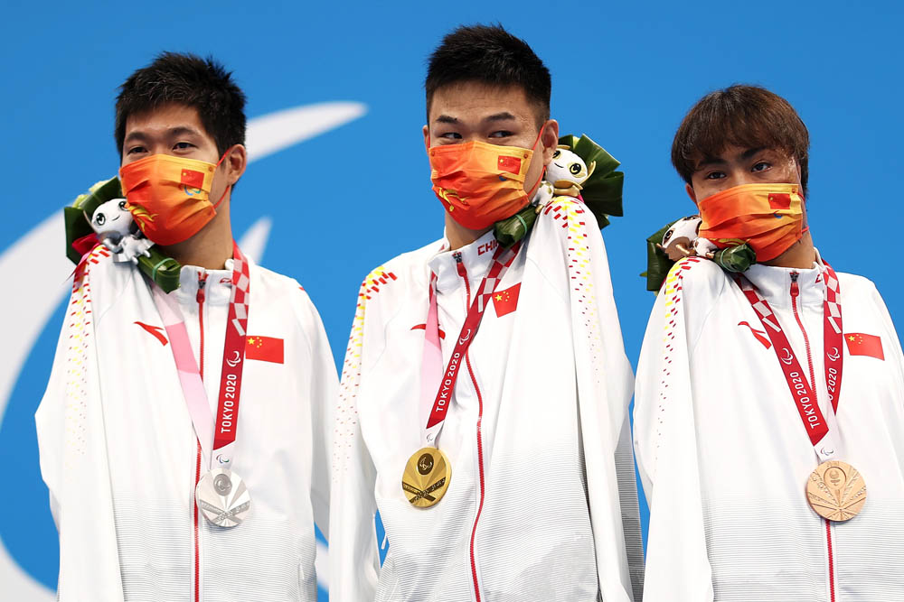 From left to right, silver medalist Wang Lichao, gold medalist Zheng Tao, and bronze medalist Yuan Weiyi pose after sweeping the men's S5 50-meter butterfly event in Tokyo, Japan, Aug. 27, 2021. Dean Mouhtaropoulos via People Visual