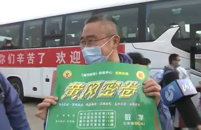 """Du Qing holds a copy of """"Huanggang Secret Exams,"""" March 2020. From 齐鲁晚报 on WeChat"""