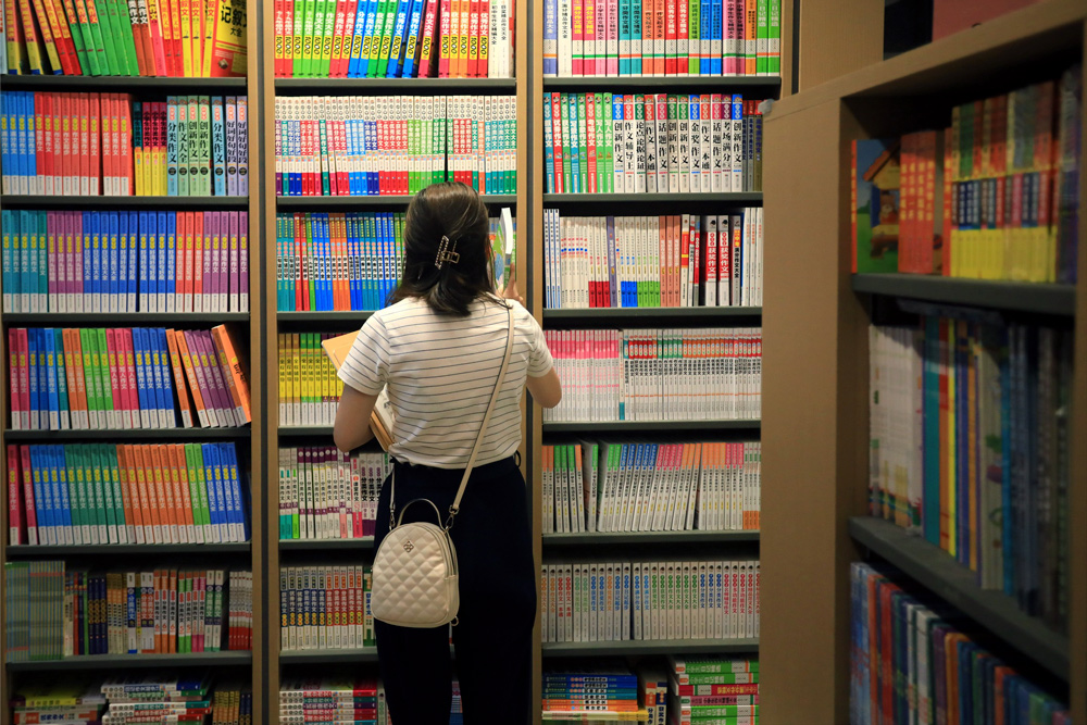 A woman picks out supplementary study materials at a bookstore in Huai'an, Jiangsu province, Aug. 29, 2021. Zhou Changguo/IC