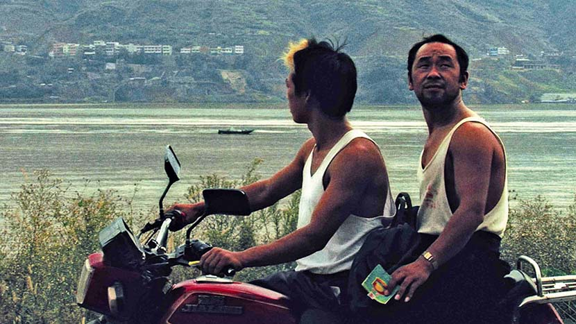 """A still from """"Still Life"""" shows the actor Han Sanming (right), who used to be a miner, riding on the back of a motorbike. From Douban"""