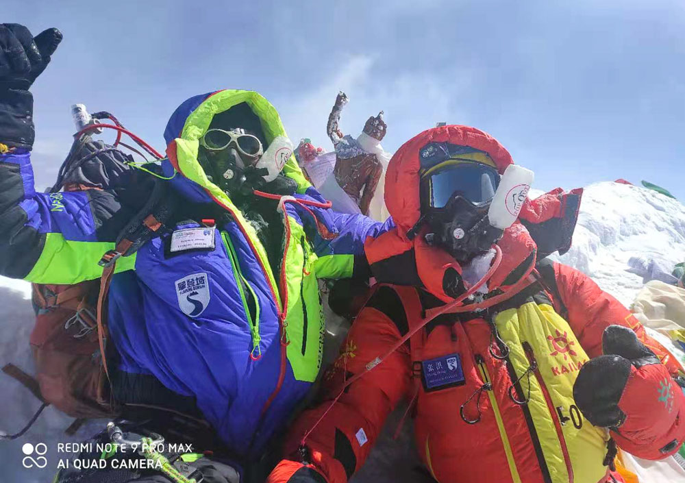 Zhang Hong (in red) poses for a photo with his team on the summit of Mount Everest, May 24, 2021. From @登峰域 on Weibo