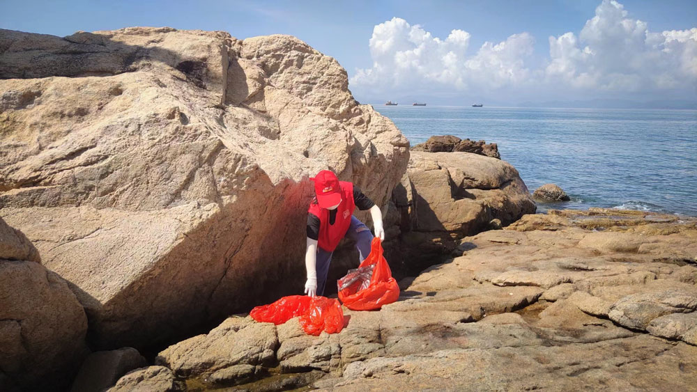 A volunteer picks up trash from between rocks on the coast of Shenzhen, Guangdong province, 2021. From 爱大鹏 on WeChat