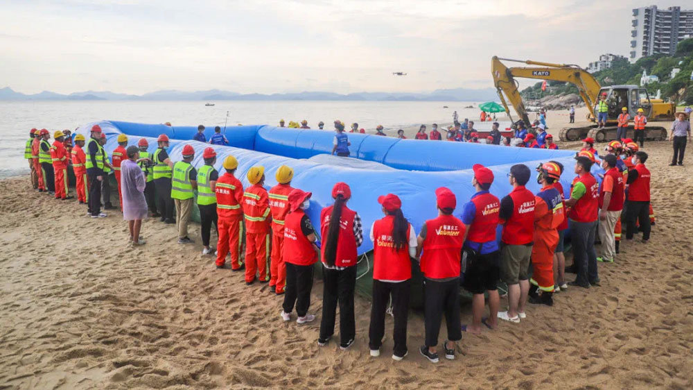 Rescue workers and volunteers take part in a whale rescue training exercise organized by the government of Dapeng New District to prepare for the possibility of Xiaobu ending up stranded, in Shenzhen, Guangdong province, July 2021. From 爱大鹏 on WeChat