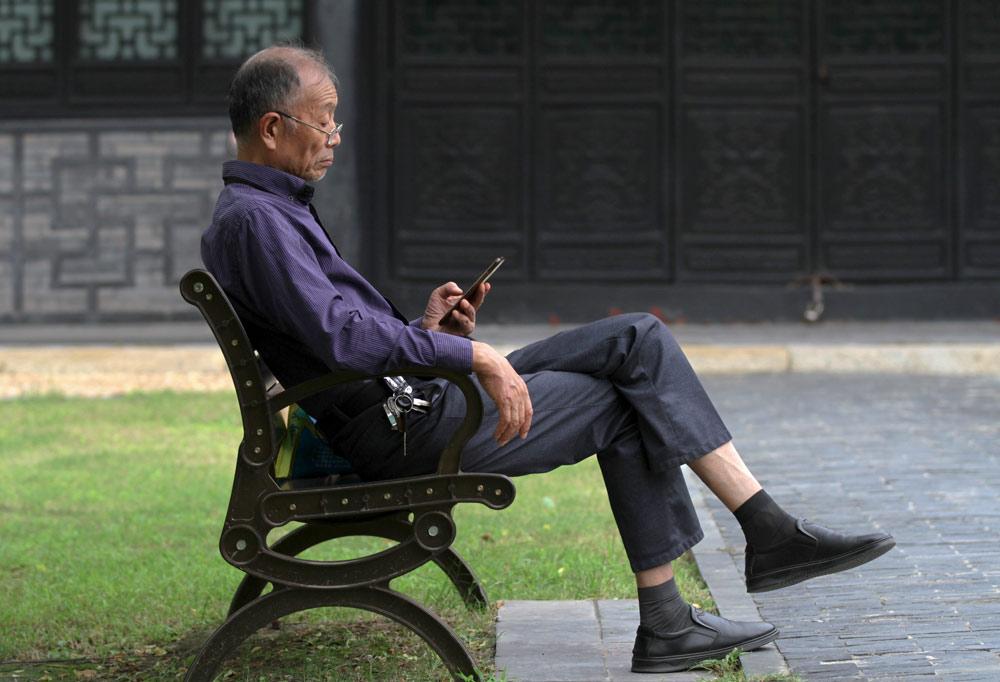 A man looks at his mobile phone in a park in Huai'an, Jiangsu province, Sept. 4, 2021. Zhou Changguo/IC