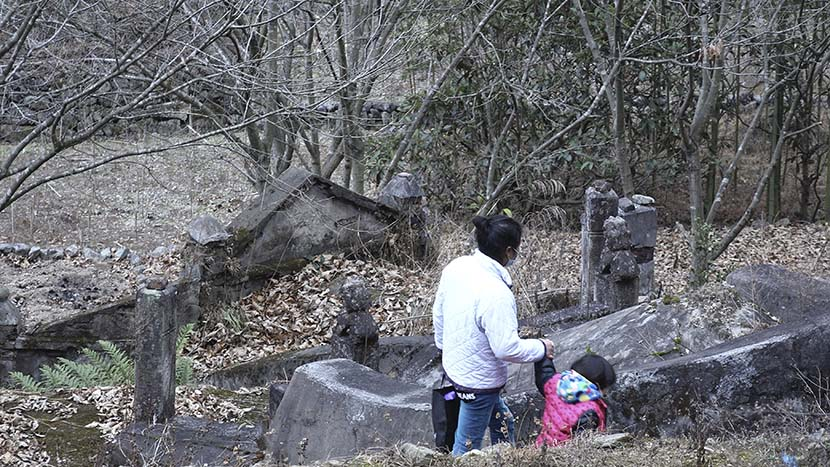 Jin Lifen visits her father's grave with her daughter in Zaokeng, Zhejiang province, Jan. 23, 2021. He Kai/The Paper