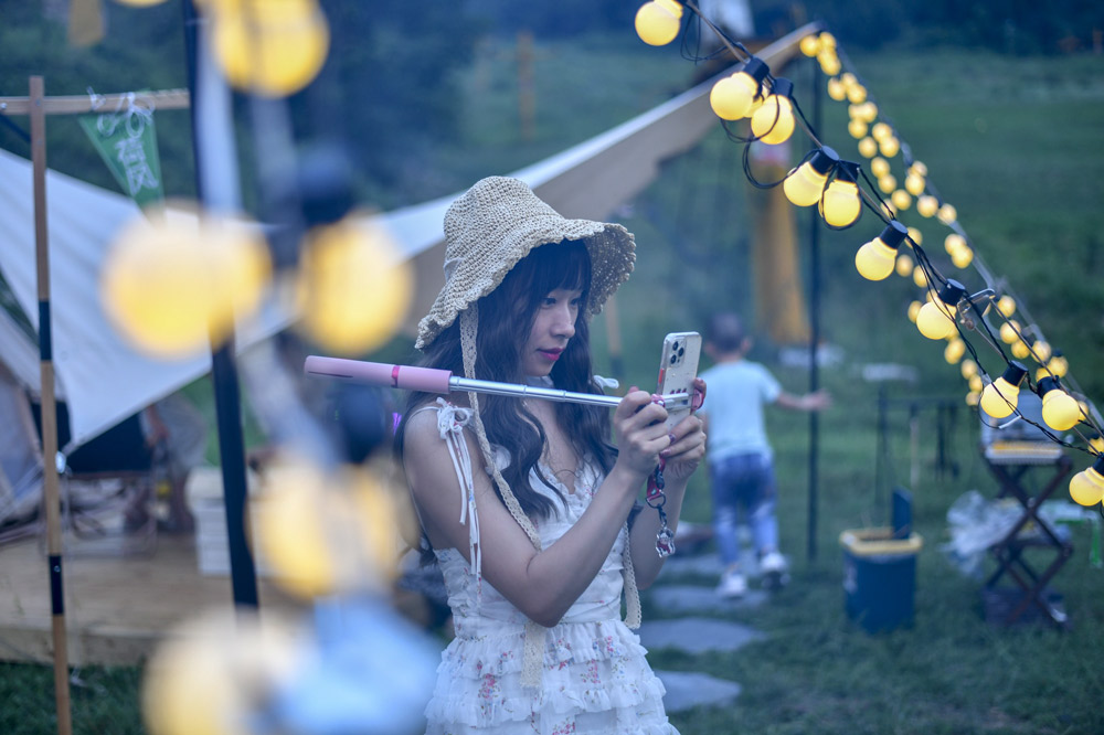 A woman checks her photos at a camping site in Jinan, Shandong province, July 2021. Yi Chu/IC