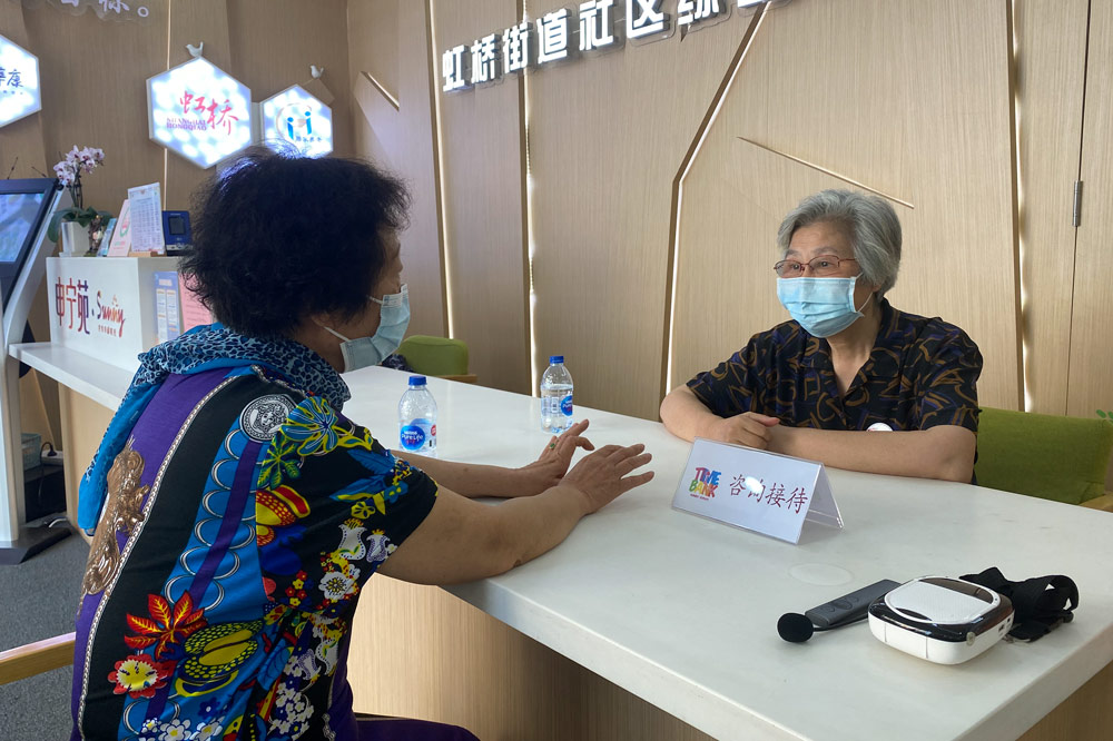 Chen Wenhua answers a local resident's questions while working as a receptionist in Hongqiao Subdistrict, Shanghai, Aug. 19, 2021. Fan Yiying/Sixth Tone