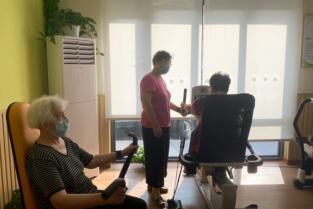 Pan Guoli (standing) shows an elderly resident how to use the machines at the gym where she works in Hongqiao Subdistrict, Shanghai, Aug. 19, 2021. Fan Yiying/Sixth Tone