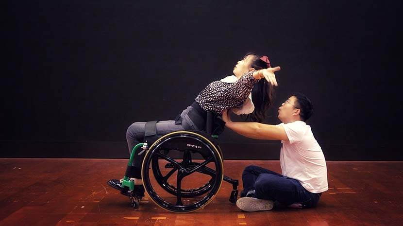Pan Jing practices wheelchair dancing with the help of her husband. Chen Si/Sixth Tone