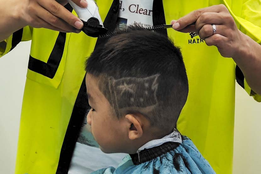 A boy gets a pattern of China's national flag on his head at a salon in Wuhan, Hubei province, Sept. 30, 2021. People Visual