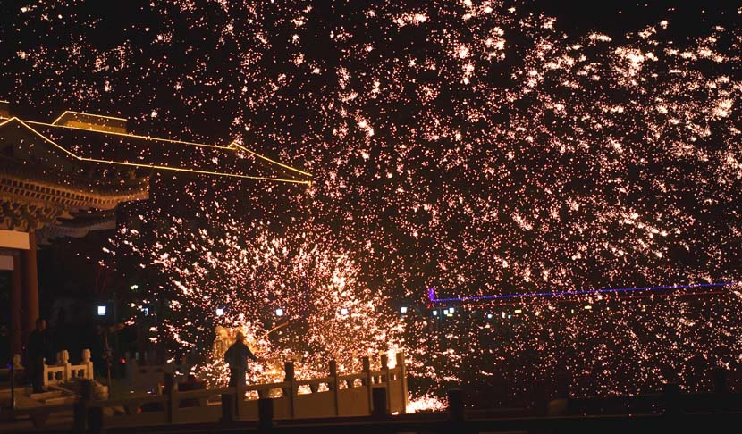 A man throws molten iron to create firework-like impression at a tourist site in Lianyungang, Jiangsu province, Oct. 1, 2021. People Visual