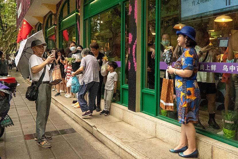 A woman poses for a photo outside Wuzhong Market in Shanghai, Oct. 9, 2021. Jiang Yaling/Sixth Tone