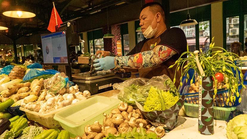 Liu Bin packs vegetables with Prada wrappers, Shanghai, Oct. 9, 2021. Jiang Yaling/Sixth Tone