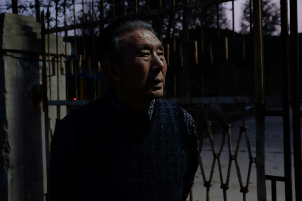 Wang Shuxuan, 84, stands in front of his factory in Huludao, Liaoning province, Oct. 2, 2021. Zhang Yiyi for Sixth Tone