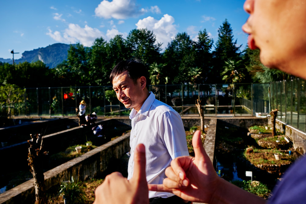 Chen Jiafa, head of the Zhangjiajie Giant Salamander National Nature Reserve Management Bureau, listens to a colleague talking about new developments in the Chinese giant salamander farming industry in Hunan province, September 2021. Wu Huiyuan/Sixth Tone
