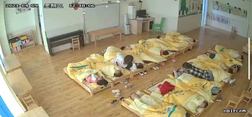 """A screenshot captured by Luo shows two teachers lying in bed with students during naptime. Luo says one of the teachers was """"spooning"""" a boy while using her phone. Courtesy of Luo Huan"""