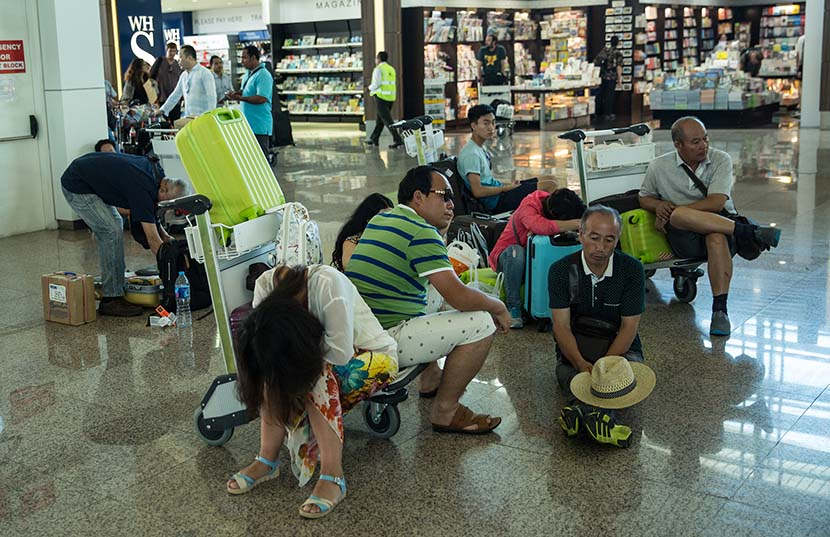 Tourists wait for flight information following delays at Ngurah Rai International Airport in Denpasar, Bali, Indonesia, July 13, 2015. Agung Parameswara/Getty Images/VCG