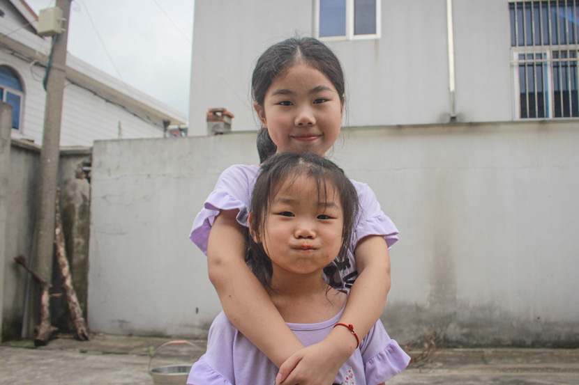 Cao Jianfen's granddaughters pose for a photo in Hongdou Village, Jiangyin, Jiangsu province, Aug. 29, 2017. Wang Yiwei/Sixth Tone