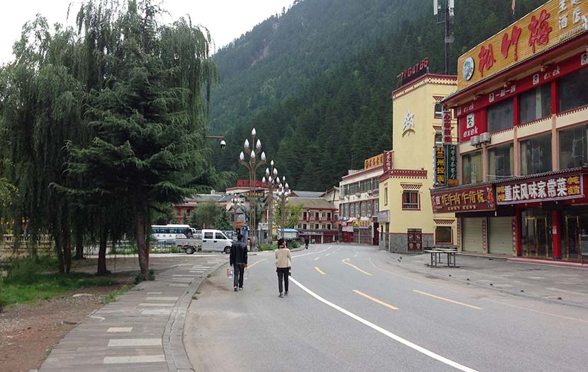 Residents walk by closed businesses outside Jiuzhaigou National Park in Sichuan province, Oct. 2, 2017. Wang Xin for Sixth Tone
