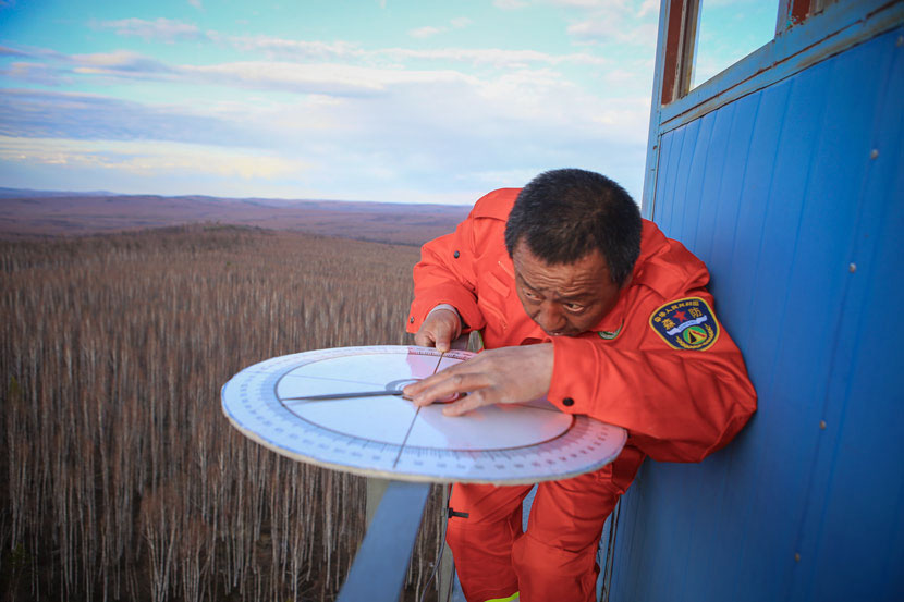 Cao Zhiguo demonstrates how to use a compass to locate a fire from his watchtower in the Greater Hinggan Mountains, Mohe County, Heilongjiang province, April 21, 2017. Zhang Yanliang/Sixth Tone