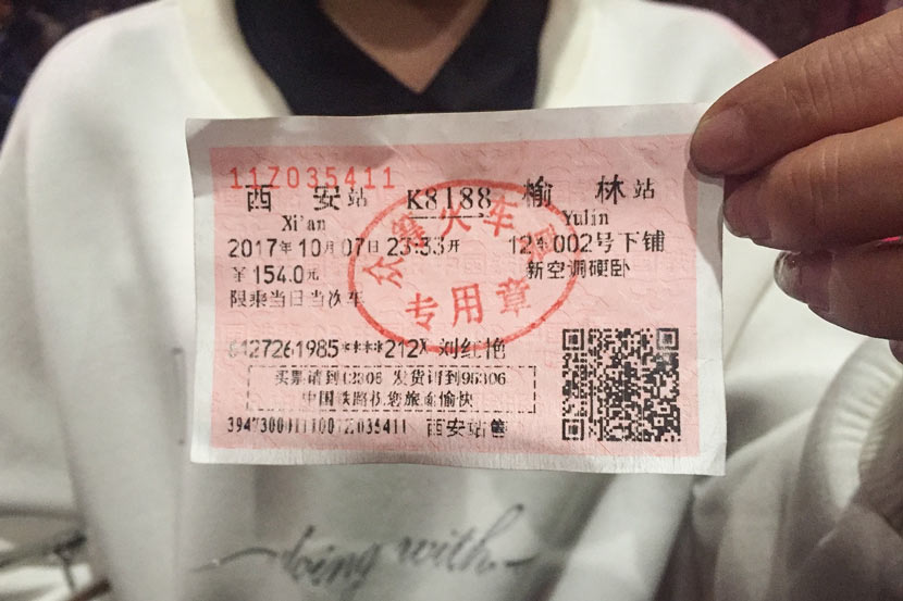 A passenger holds her ticket for a crowdfunded train at a railway station in Xi'an, Shaanxi province, Oct. 7, 2017. VCG