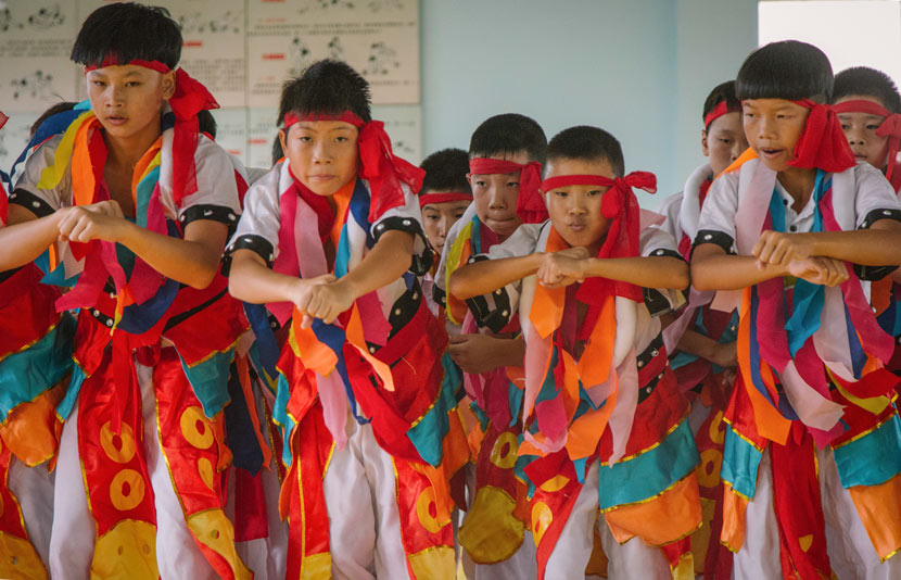 Young wrestlers in traditional ethnic Mongolian costumes perform a mix of wrestling moves and Mongolian dance at Matian Central Primary School in Luxi County, Jiangxi province, Sept. 5, 2017. Wu Huiyuan/Sixth Tone