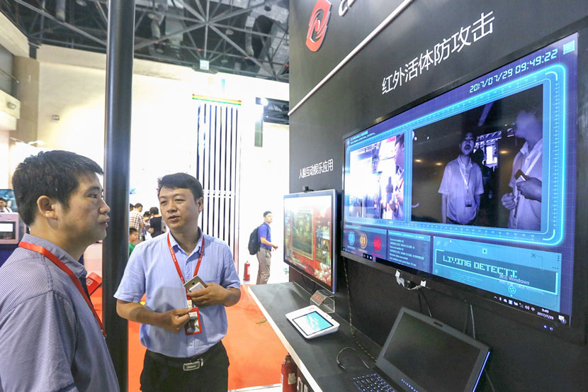A CloudWalk staff member introduces the company's facial recognition technology during the annual China International Financial Exhibition in Beijing, July 29, 2017. Lei Kesi/IC