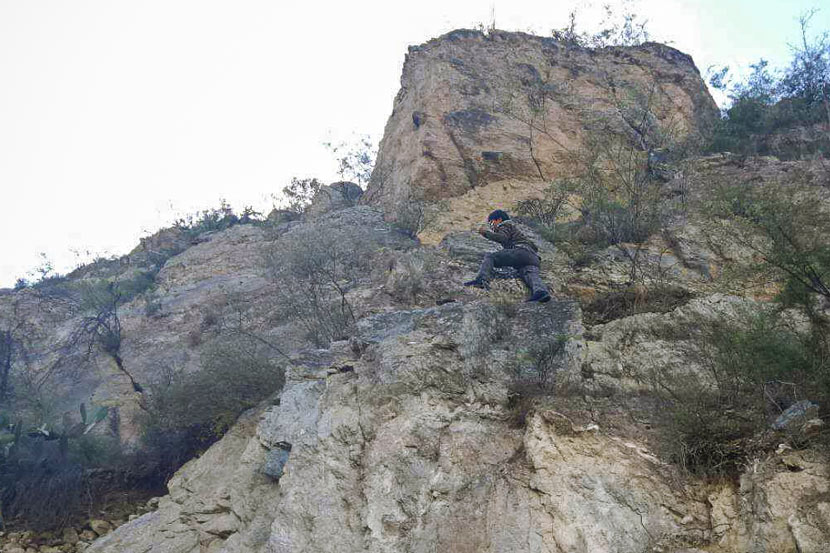 A member of Liu Jiewen's meteorite-hunting group scales a cliff in Deqen County, Yunnan province, October 2017. Courtesy of Liu Jiewen