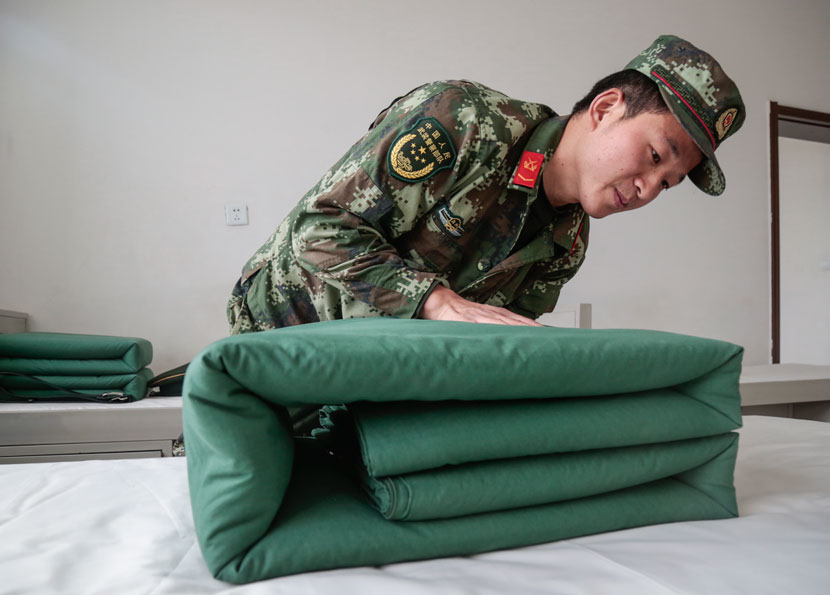 Shao Xiaowei, 26, folds his bedding at the military base where he is stationed in Yakeshi, Inner Mongolia Autonomous Region, Sept. 23, 2017. Li You/Sixth Tone