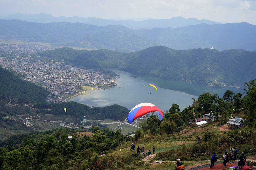 Paragliders soar over Phewa Lake in Pokhara, Nepal, April 27, 2014. Sajjad Hussain/VCG