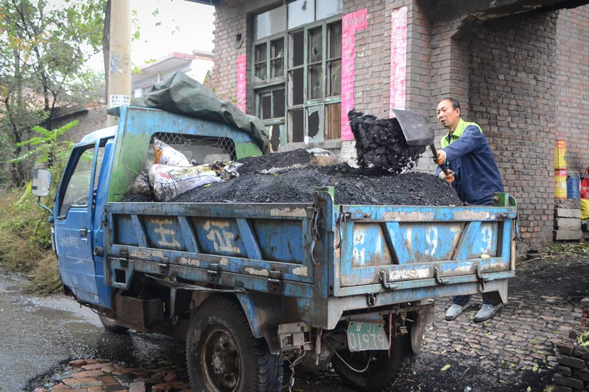 Su Jianhong shovels coal from his yard into a three-wheeled truck in Taiyuan, Shanxi province, Oct. 18, 2017.  Fan Liya/Sixth Tone