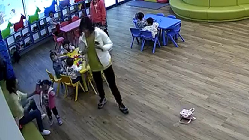 A screenshot from a surveillance video at the Ctrip day care center shows an employee pushing a little girl. From Weibo