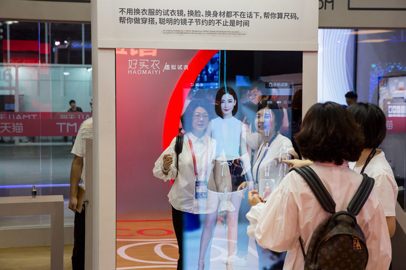 A customer uses a smart mirror to try on clothes virtually during Alibaba's annual Cloud Computing Conference in Hangzhou, Zhejiang province, Oct. 11, 2017. Shi Yangkun/Sixth Tone