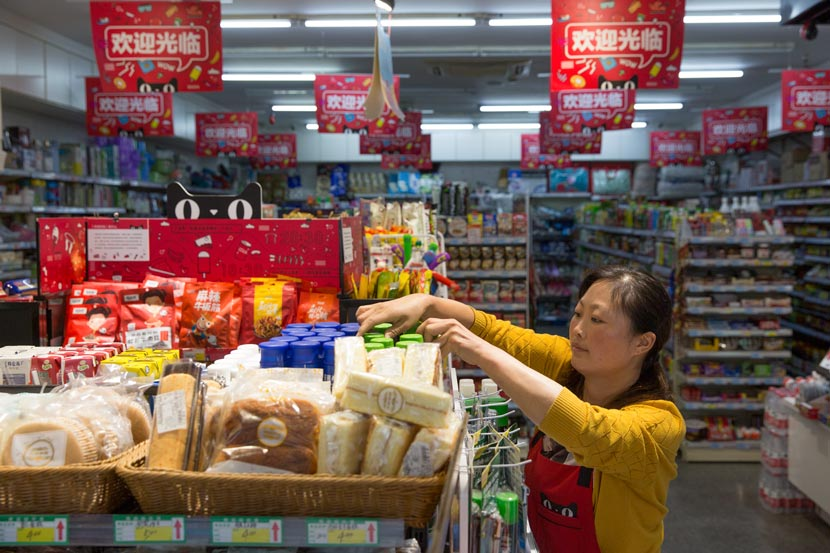 An employee arranges products on a shelf at the Tmall Weijun convenience store in Hangzhou, Zhejiang province, Oct. 11, 2017. Shi Yangkun/Sixth Tone