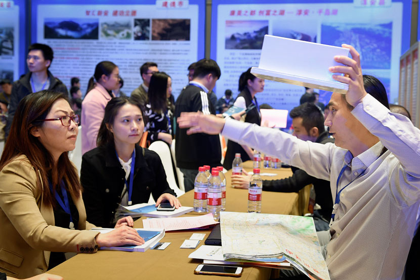 A graduate (right) speaks with prospective employers at a job fair in Hangzhou, Zhejiang province, Nov. 8, 2017. Li Zhong/VCG