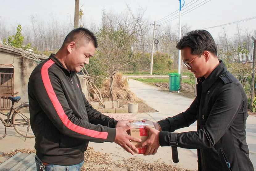Deliveryman Zhang Xiaoyan (right) hands a package to a JD.com customer in Zhangwei Township, Jiangsu province, July 27, 2017. Chen Na/Sixth Tone