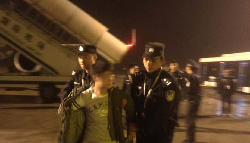 The passenger who caused a disturbance midflight is escorted away by police after the plane landed safely in Changsha, Hunan province, Nov. 14, 2017. From the Weibo account of the Hunan police