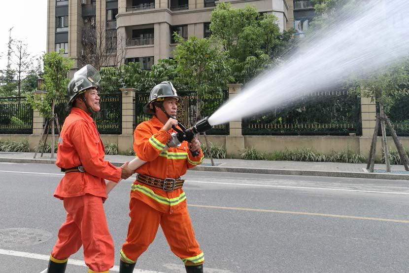 Wang Defa (right) aims a water hose during a firefighting drill in Fuzhou, Fujian province, Sept. 12, 2017. Yan Jie/Sixth Tone