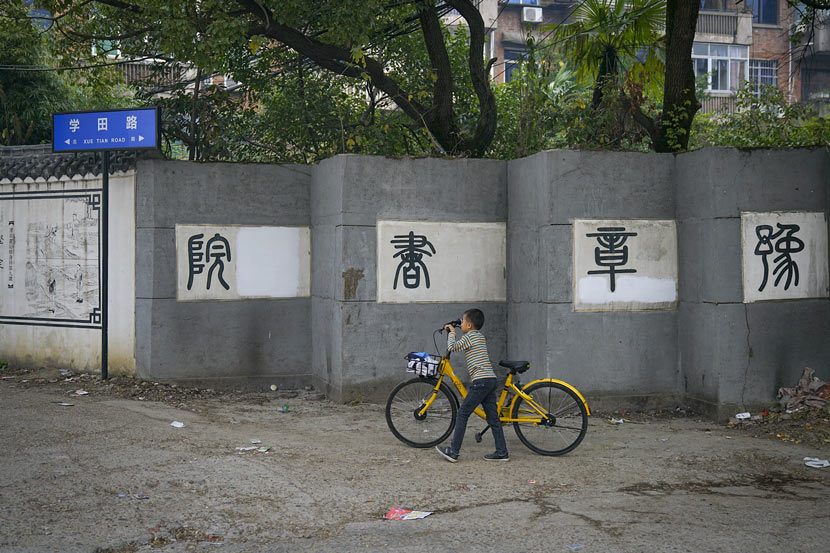 A child walks with a shared bike in front of the outer wall of Yuzhang Academy in Nanchang, Jiangxi province, Nov. 6, 2017. Yang Yifan/Caixin/VCG