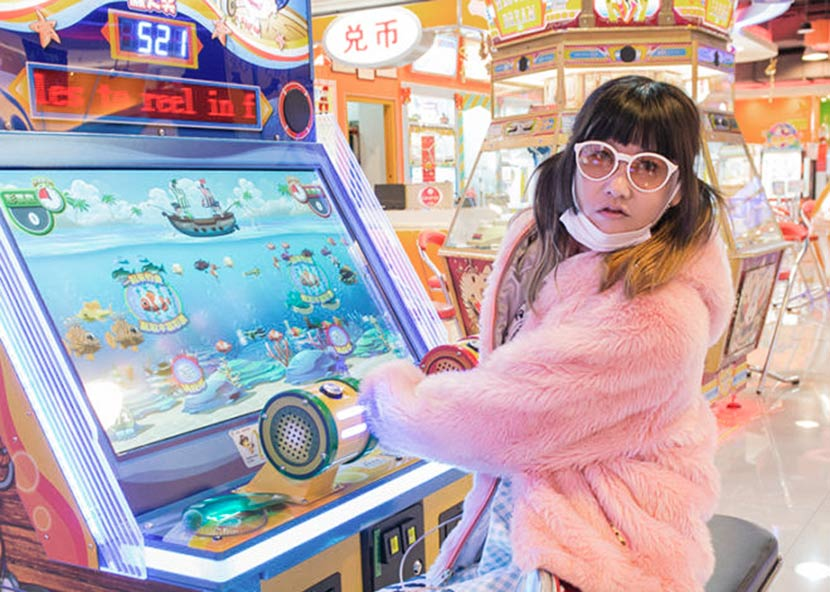 Lu Yang poses for a photo at an arcade. From the artist's website