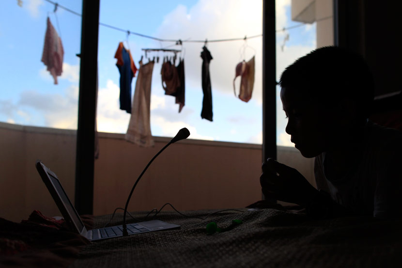 A boy plays on a computer in his family's rental apartment in Shanghai, July 31, 2012. Wang Juliang for Sixth Tone
