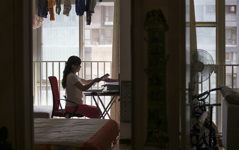 A young mother studies for her certified tax adviser exam at her home in Xi'an, Shaanxi province, May 15, 2015. Huang Lijian/VCG